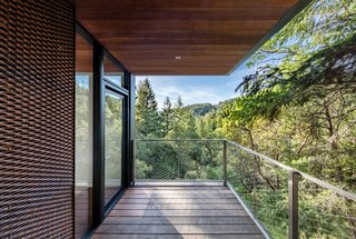 The flat roof features deep overhangs to shield the interior from solar heat gain.