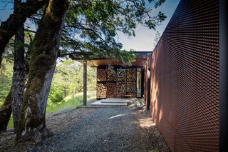 All three flat-roofed buildings are clad in weathering steel expanded metal rainscreens, while floor-to-ceiling operable glass walls bring the outdoors in.