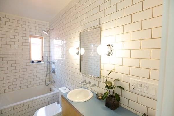 Subway tile lines the compact bathroom that's fitted out with low-flow Kohler fixtures.