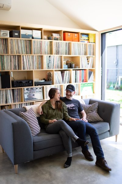 Scott Mooney and Lauren Shumaker sit on their living room couch purchased from a local business, Perch Furniture.