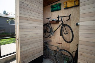 The custom storage solutions  can hold a variety of items including bicycles and bicycle trailers, house and gardening tools, camping equipment, and the outdoor grill.