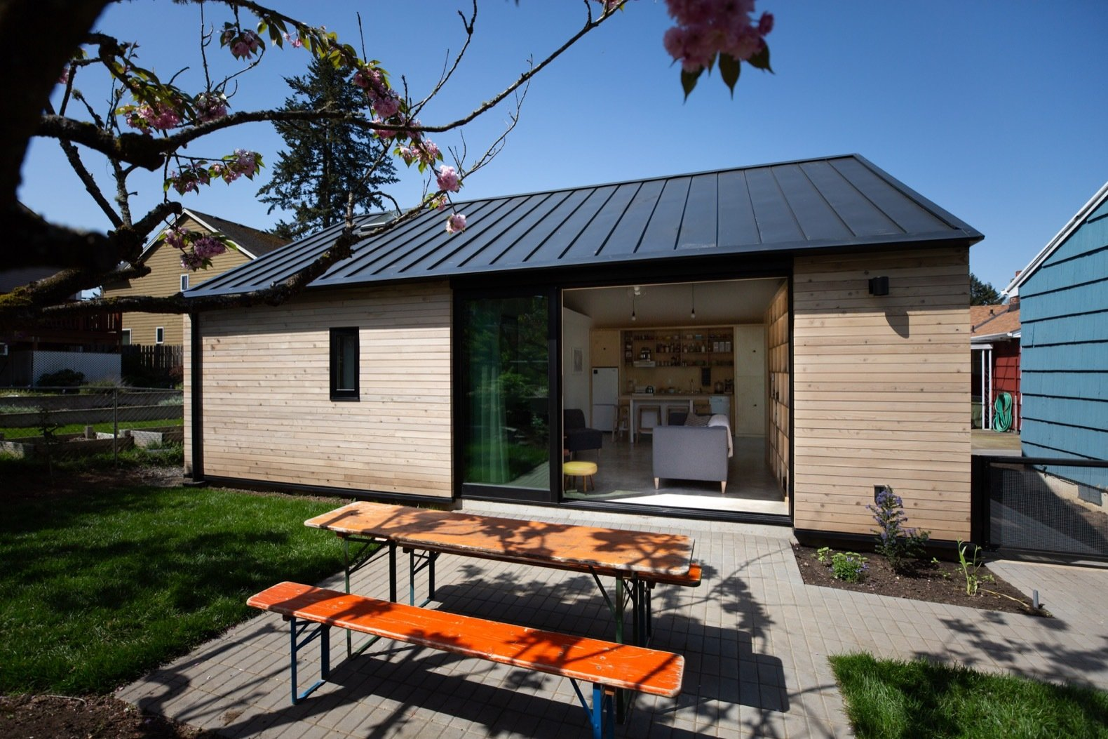 Outdoor, Grass, Back Yard, and Small Patio, Porch, Deck A dark gray standing seam metal roof tops the building with metal eaves that match the depth of the existing home.   Photo 6 of 20 in Budget Breakdown: A Portland Couple Design and Build a Compact Home For $222K