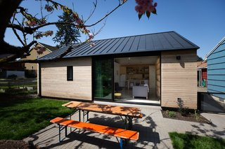 The living space seamlessly connects to an outdoor patio with seating. A dark gray, standing-seam metal roof tops the building with metal eaves that match the depth of the existing home.