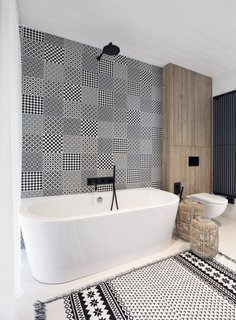 Black accents and patterns breath life into the bathroom with a freestanding tub.