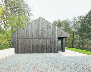 The home is accessed from the west, where the garage is hidden behind a charred timber door.