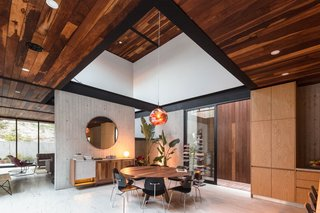 Tom Dixon's mesmerizing Melt Pendant Lamp hangs from a raised ceiling over the dining table. The dining room credenza is Jorge's original design.