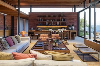 The outdoor landscape is brought indoors through the continuation of the red concrete walls and ample glazing.