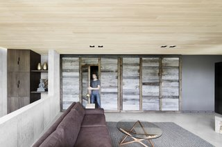 The timber doors of a former garage have been repurposed into a room partition that separates the main living area from the rest of the ground floor.