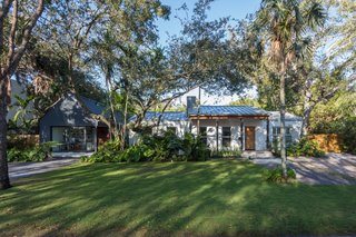 The home is nestled in a lushly planted landscape with tropical flora and live oaks.