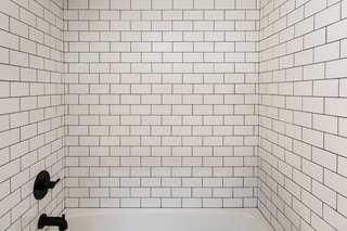 Subway tile surrounds the bathtub in the second bathroom.