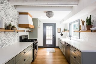 The white countertops are made from concrete and the wooden cabinets have been painted a subtle shade of sage. The floors are white oak hardwood.