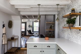 Twin pendant lights hang above the breakfast bar at the far end of the kitchen.