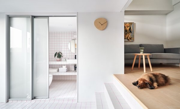 An opaque sliding glass door separates the bathroom from the dining area. White tile with pink-colored grout ties the two spaces together.