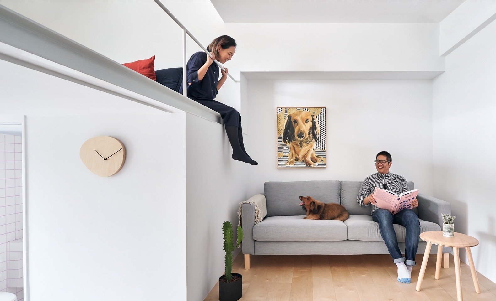 Living Room, Sofa, Light Hardwood Floor, and Coffee Tables The mezzanine safety railing is made thin and painted white to minimize its appearance.    Photo 6 of 17 in A Tiny Taipei Apartment Pursues Muji-Like Minimalism For $35K