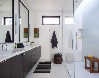 Metalword porcelain tile covers the floor of the bathroom. This space is made bright and airy thanks to the mostly white color scheme and skylight placed over the shower.