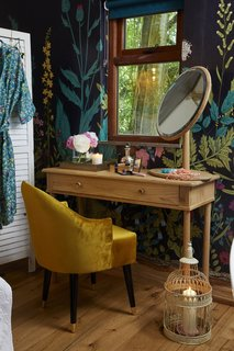 Guests can slip into the plush Emi Velvet Tub Chair while getting ready at the vanity, which is framed by a gorgeous Botanical Fleur Wallpaper Wall Mural. The large mirror is from Adame.