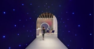 A deep blue plywood tunnel punctuated with twinkling, star-like lights leads from the entrance to the reception and lounge.