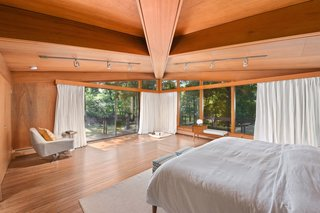 Sliding glass doors connect the master suite to the wraparound deck.
