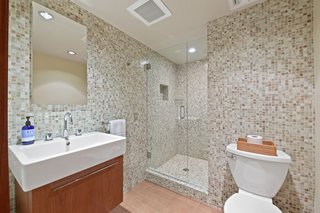 The ensuite bath features tiled walls and a glass-enclosed shower.