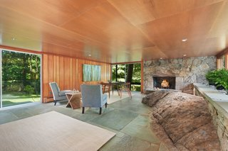 One of the most dramatic examples of site integration, the family room is built around a natural rock outcropping and finished with a slate floor and stone fireplace.