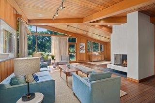 A fireplace is located in the middle of the L-shaped great room.