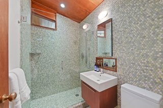 Located off the hallway, this bathroom features a glass-enclosed shower and high-end fixtures.