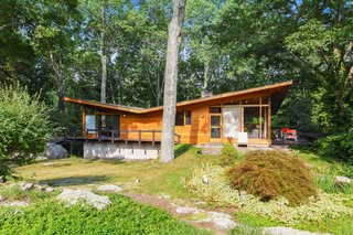 Built in 1956 by renowned local builder Vito Fosella, the two-story home embraces the wooded landscape with an exterior clad in teak, mahogany, and stone. The roof is tar and gravel.