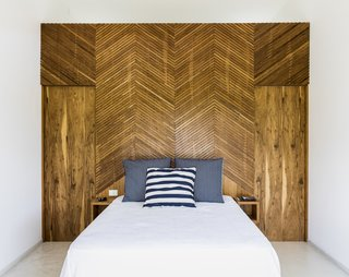 The chevron pattern is brought indoors to the bedrooms. Pivoting doors on either side of the bed provide access to the bathroom.