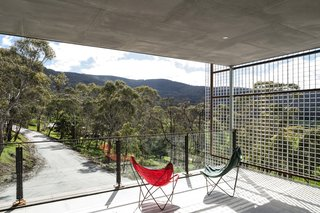 A deep roof overhang creates a sheltered outdoor patio for enjoying north-facing views of the landscape.