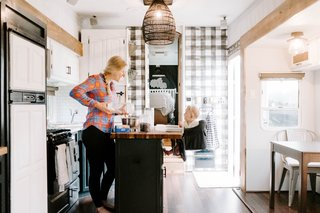 """When people walk into the RV, the kitchen is the first thing they notice,"" notes Lauren. ""We added a stick-on backsplash, painted the upper and lower cabinets, added the utensil holder, knife magnet, painted the spice rack, and added the butcher block island top. We cut it a little long so there was enough overhang for our daughter's highchair."""
