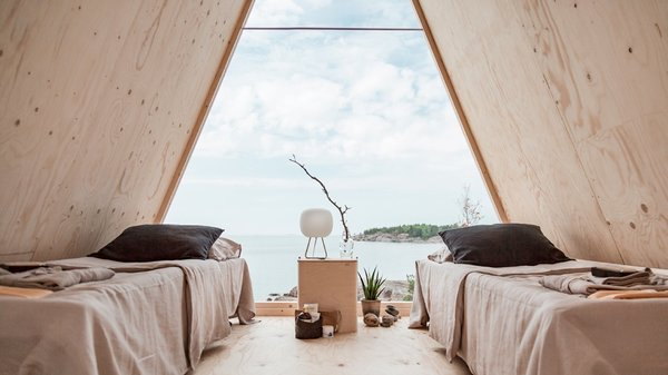 Overlooking stunning views of the archipelago, the one-bedroom building is furnished with two camping beds, a small cooking nook, and other locally procured sustainable furnishings.