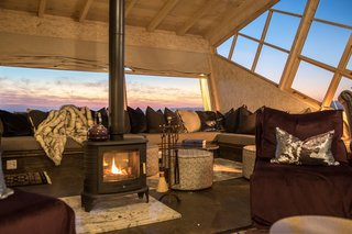 The cozy lounge with a wood-burning stove overlooks views of the northern rocky hills.