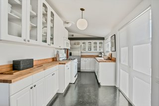 Beautiful butcher-block countertops lend a sense of warmth to the all-white kitchen with modern fixtures.