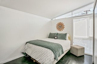 The second bedroom with a full-height glazing overlooks the backyard pool.