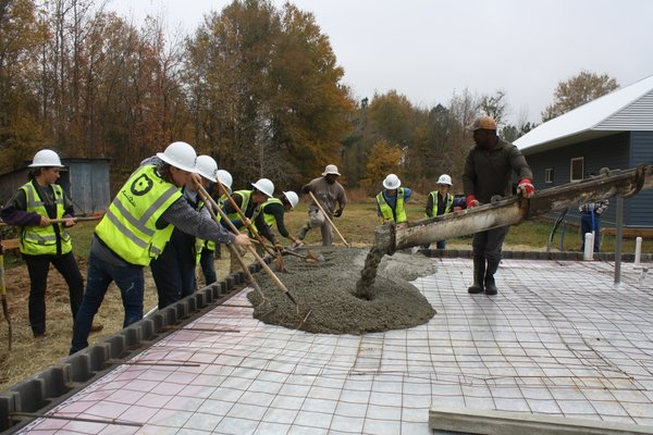3rd-Year fall semester students from Ree's Home project working on the elevated slab foundation, which includes a perimeter wall of CMU block compacted with engineered dirt and filled with gravel.