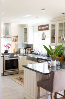 The kitchen morphed into a bright, airy space. An island hood replaced the cabinets over the stove, while pendant lights take the place of the cabinets that had been atop the bar area. All cabinets were replaced, and new Blue Pearl granite countertops were installed.