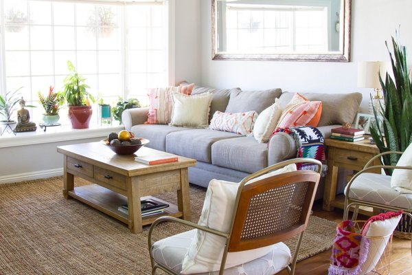 New paint and furnishings have transformed the remodeled sitting room of the Burnett Bungalow. A jute rug adds an earthy touch to the boho-inspired space.
