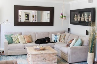 In addition to contemporary furnishings, the updated living room includes newly painted ceilings (swish coffee) along with new baseboards and crown moulding. The couple's black lab, Lola, can be seen on the sectional, which was purchased from Living Spaces.