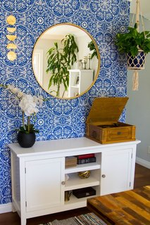 Janelle turned the divider wall next to the dining table into a focal point with a peel-and-stick wallpaper from Target's Opalhouse collection. Various knickknacks, many of which were thrifted, are put on display.