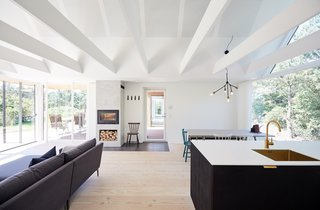 A white beamed ceiling adds structure to the open and airy living space bookended by immersive views of nature.