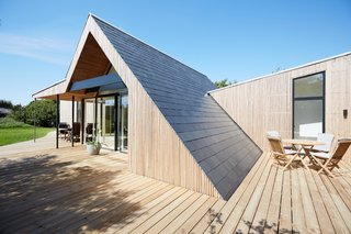 The gabled roof extends to the timber deck and is covered in natural slate tiles.