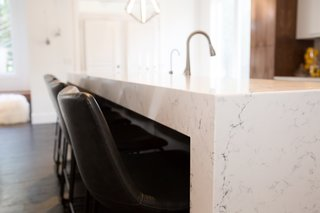 A close up of Caesarstone's 'White Attica,' a polished marble-like slab with delicate gray veining.