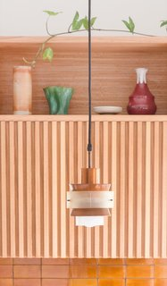 Refurbished vintage copper pendant lights hang above the kitchen's handmade Manuka honey-colored tiles.