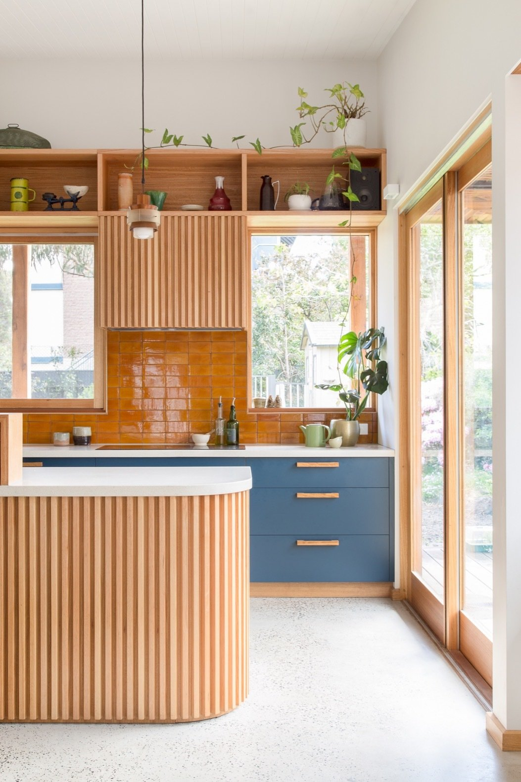 Kitchen, Ceramic Tile Backsplashe, Wood Cabinet, Engineered Quartz Counter, Concrete Floor, Pendant Lighting, Cooktops, and Colorful Cabinet Shielded by overhanging eaves, ample northern glazing lets in an abundance of natural light and views of the outdoors.   Photo 6 of 15 in A Cramped Bungalow Is Reborn as an Eco-Minded Abode For Two Gardeners