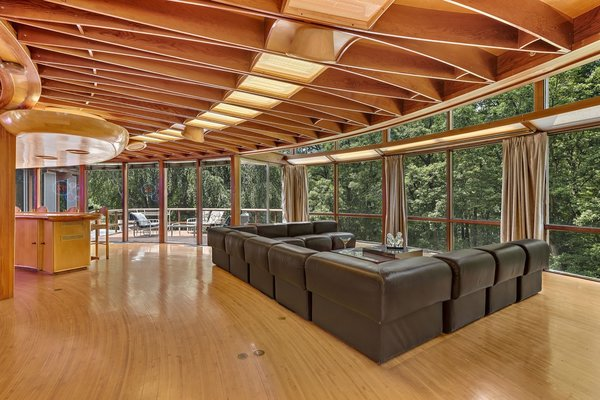 Full-height glazing wraps around the house for spectacular views of the woods.