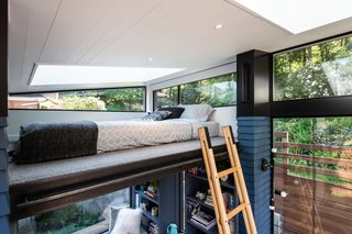 Accessed via collapsible ladder, the 58-square-foot loft bedroom with a queen mattress is located beneath an angled tongue-and-groove cedar ceiling that's painted white and punctuated by a large skylight. The floor is wool carpet.