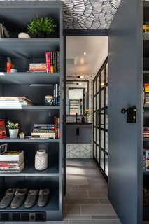 The entrance to the bathroom is tucked between two bookshelves.