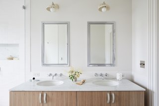 The updated master bathroom includes a double vanity with a Calacatta Michelangelo marble countertop with chrome plumbing fixtures from Waterworks Easton.