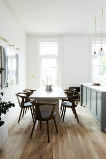The kitchen and dining area are made to feel bright and airy with minimalist decor and walls painted Sherwin Williams Origami White. The lights hanging over the island are Allied Maker's Blobe pendants.
