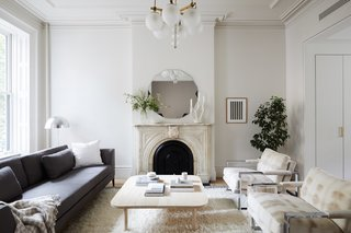 The living room gains an airy and modern update with new crown molding and walls painted Sherwin Williams Origami White. The clients also restored the living room's marble fireplace and painted the grate Benjamin Moore Black.